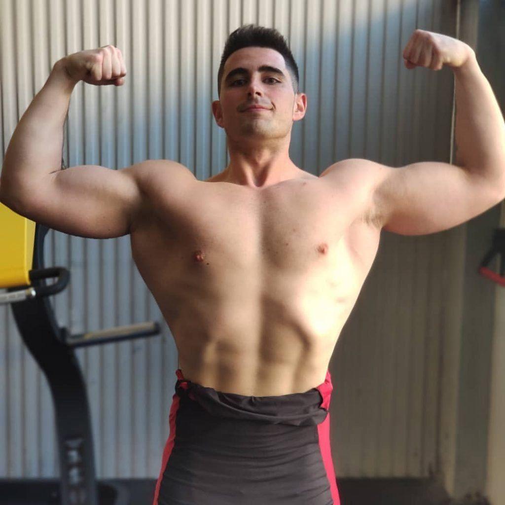 Marcos Conquer con pose de doble biceps